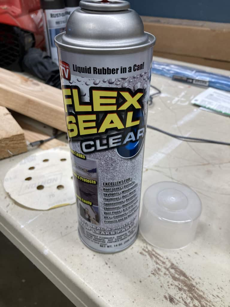 Applying flex seal to the feet of the ladder rail.