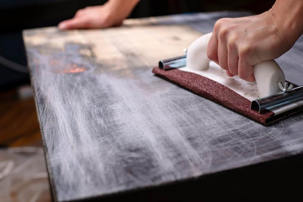 Sanding a table top to refinish it.