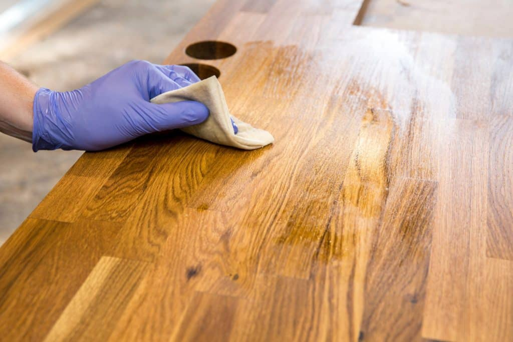 Rubbing a penetrating oil into the wood surface.